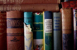 The spines of books in a bookshelf. Titles include Treasure Island, Twenty Thousand Leagues Under the Sea and Fairy Tales from Hans Andersen.