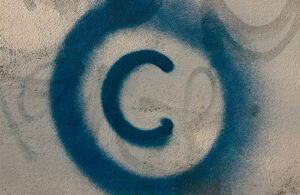A blue copyright symbol is spray painted on a cream-coloured wall.