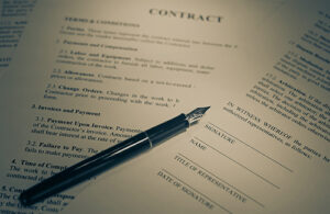 A black fountain pen lays on top of pages of a contract.
