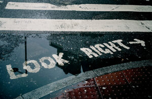 White words reading 'Look right' are on the surface of a bitumen road.