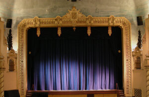 Purple curtains are drawn across a stage framed by an opulent gold frame.
