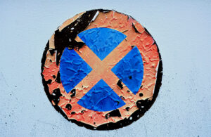A peeling sticker with a red circle and an x crossed over a blue background.