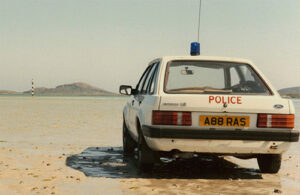 A Ford Escort is being used as a Police car. A blue flashing light has been affixed to the roof and the word 'Police' has been painted on the car boot.