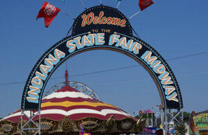 A large arch with the words, 'Welcome to the Indiana State Fair Midway' painted on it.