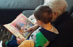A grandmother and her grandson sit together reading a picture book.