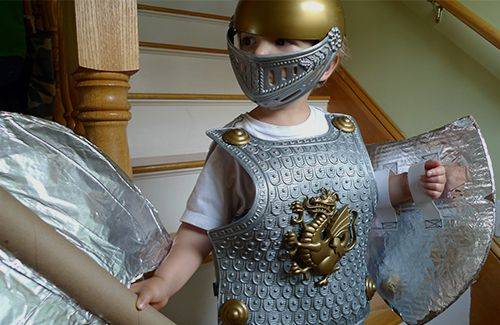 A child wearing a knight costume and holding a home-made shield and battle axe made out of cardboard and aluminium foil.