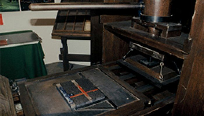 A photo of a replica Guttenberg printing press setup to print a page from the bible.